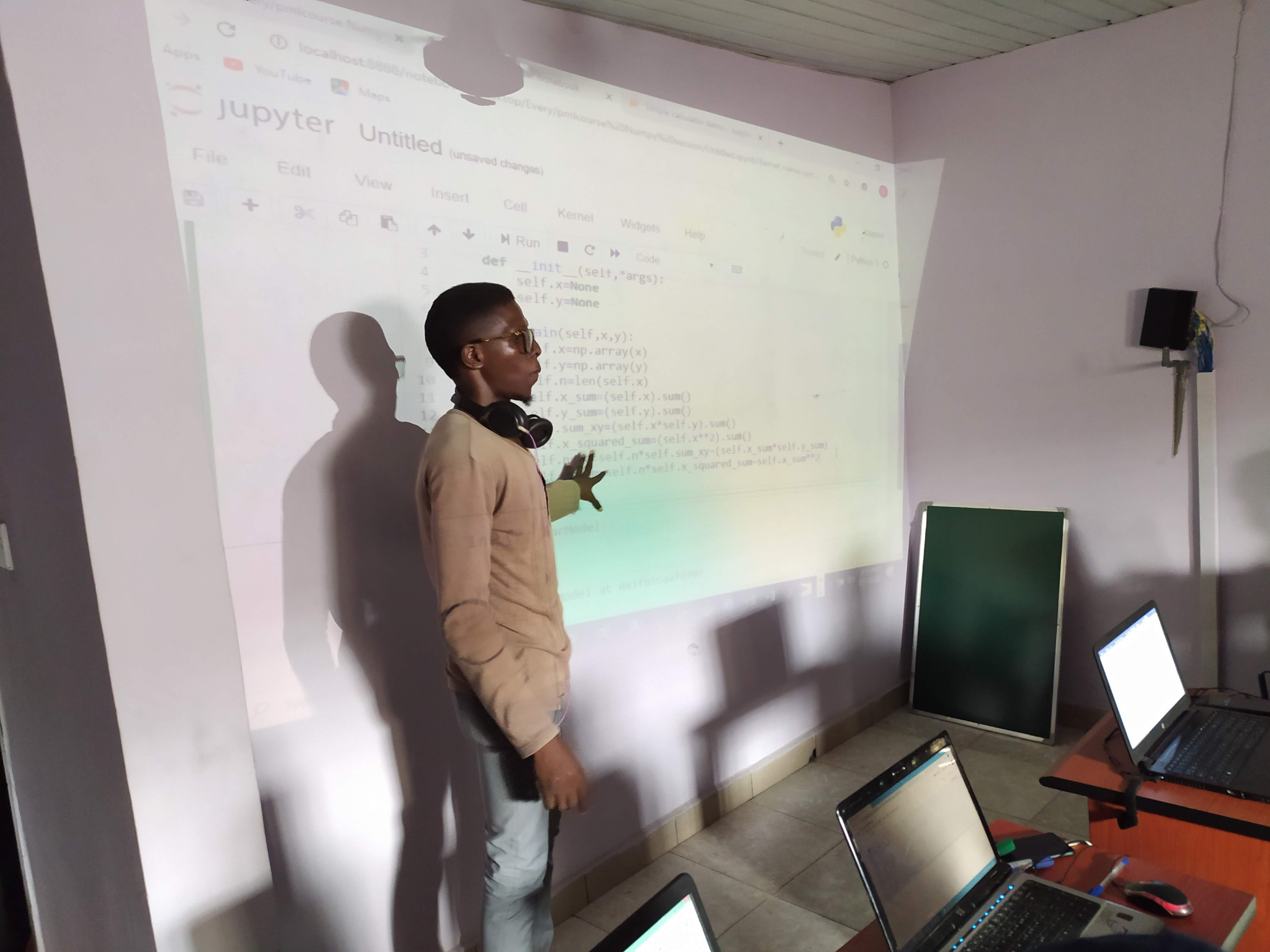 A man wearing a brown shirt is pointing to a projected screen containing Python code.jpg
