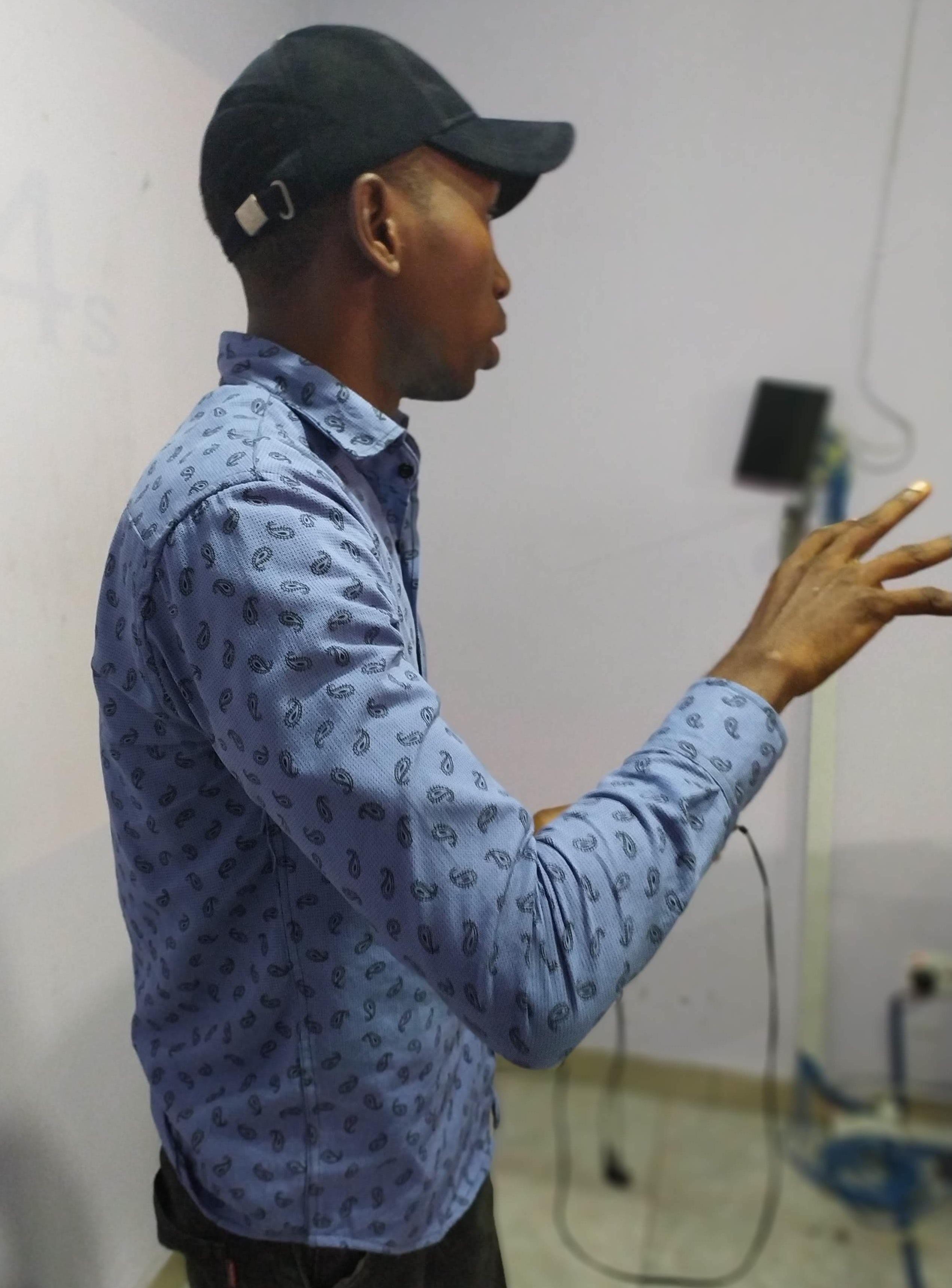 A man in blue shirt and black cap explaining a concept.jpg