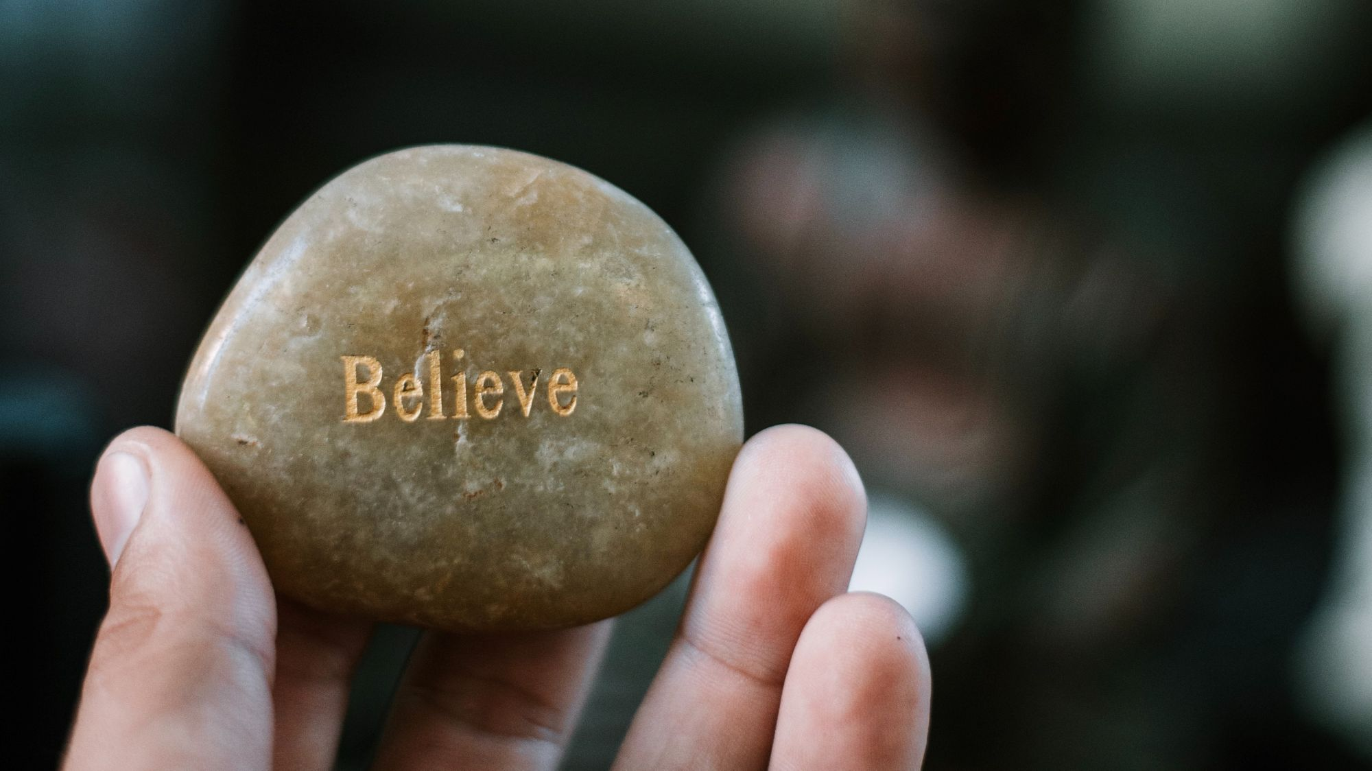 person holding brown stone with believe print photo – Free Human Image on Unsplash