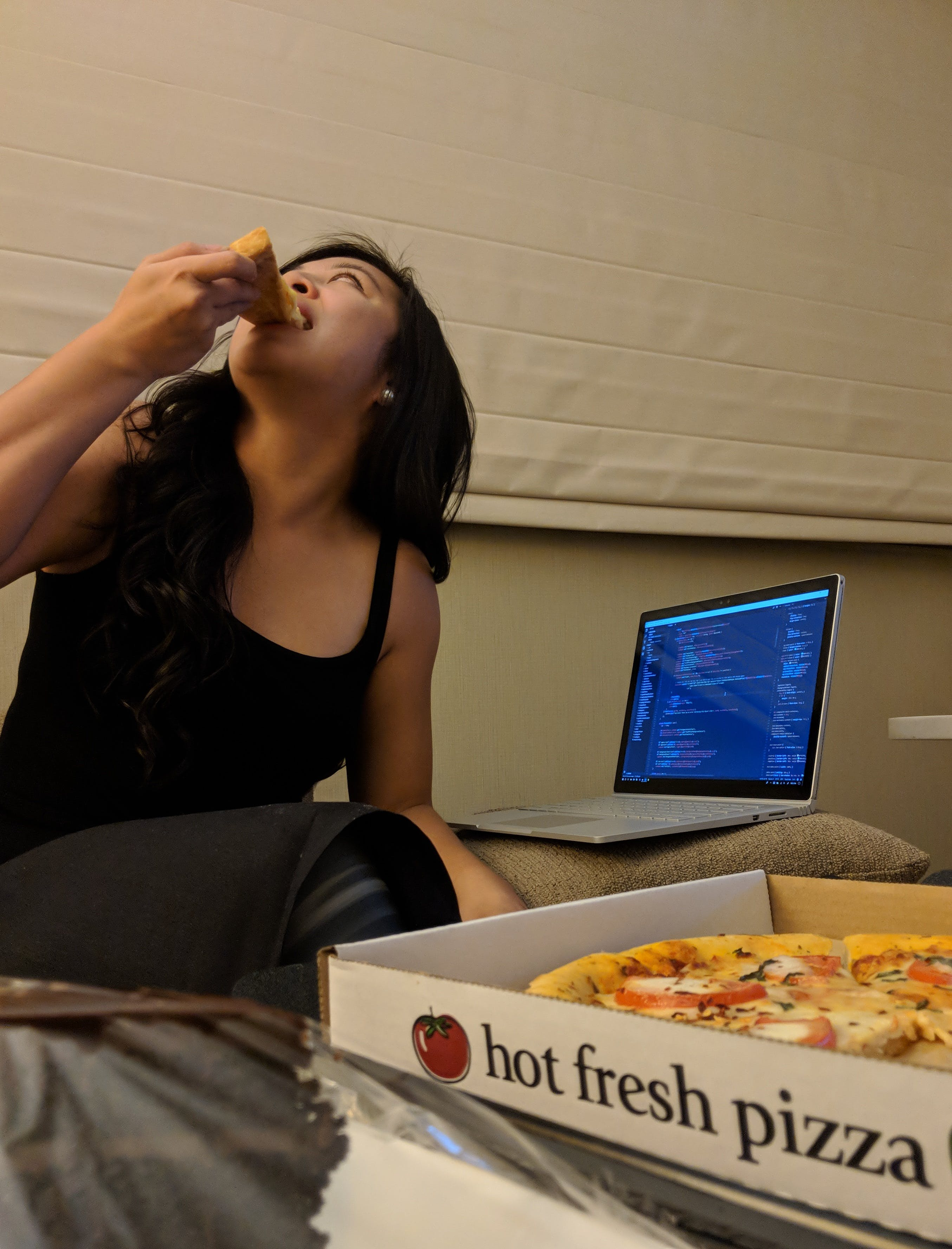 Adrienne eating a pizza in her hotel room.