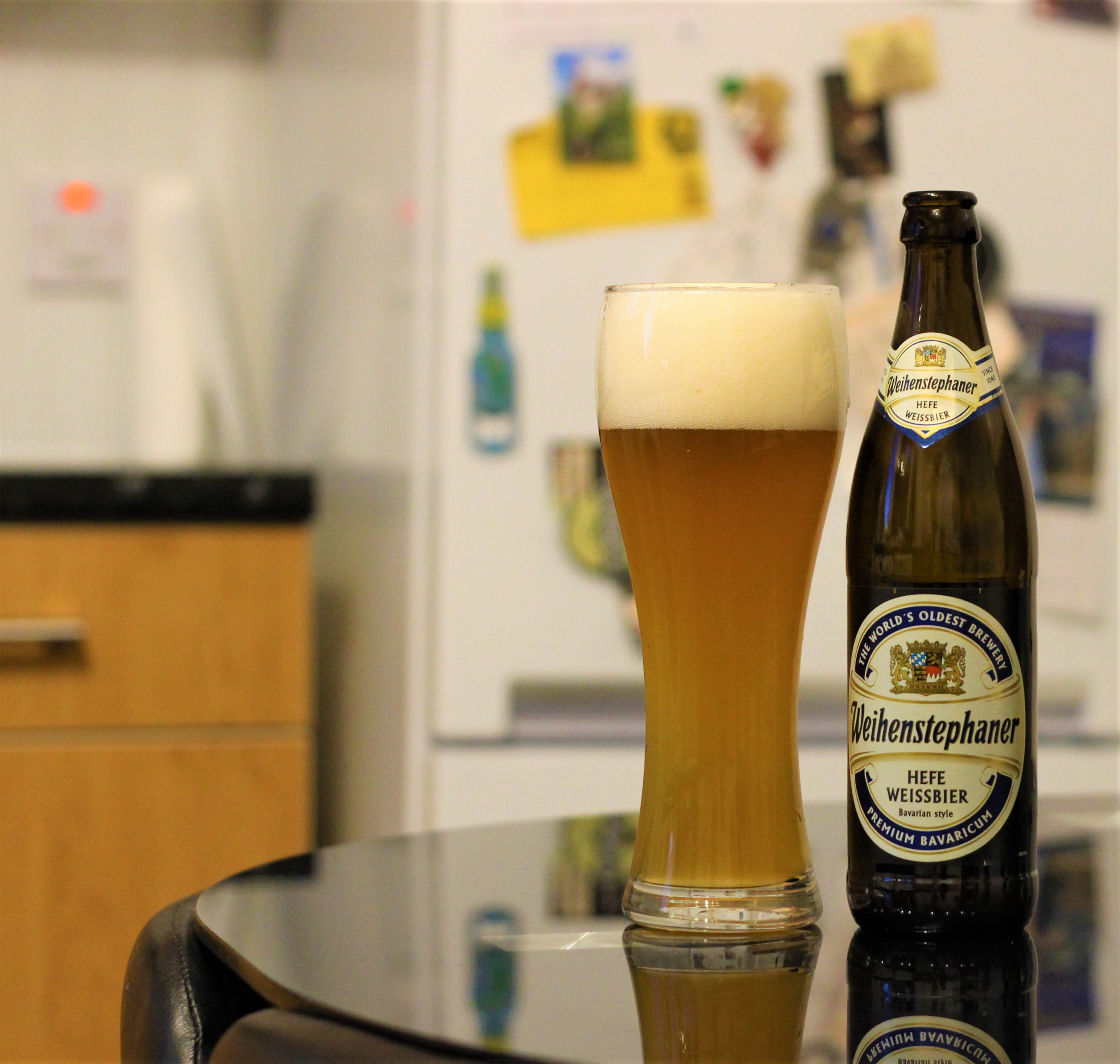 bottle of weihenstephaner sitting on a table next to a full glass of the beer