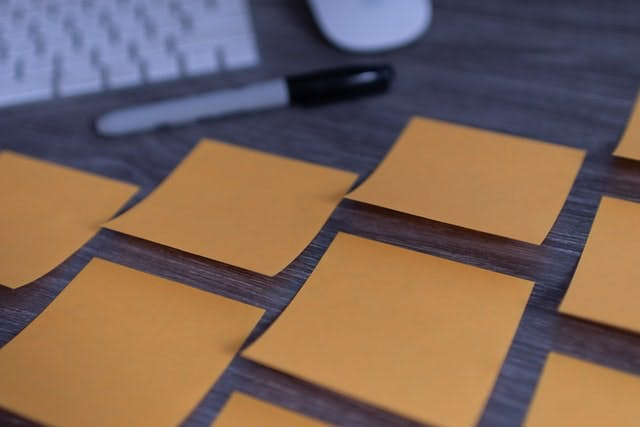 Group of blank sticky notes on a desk with a sharpie marker
