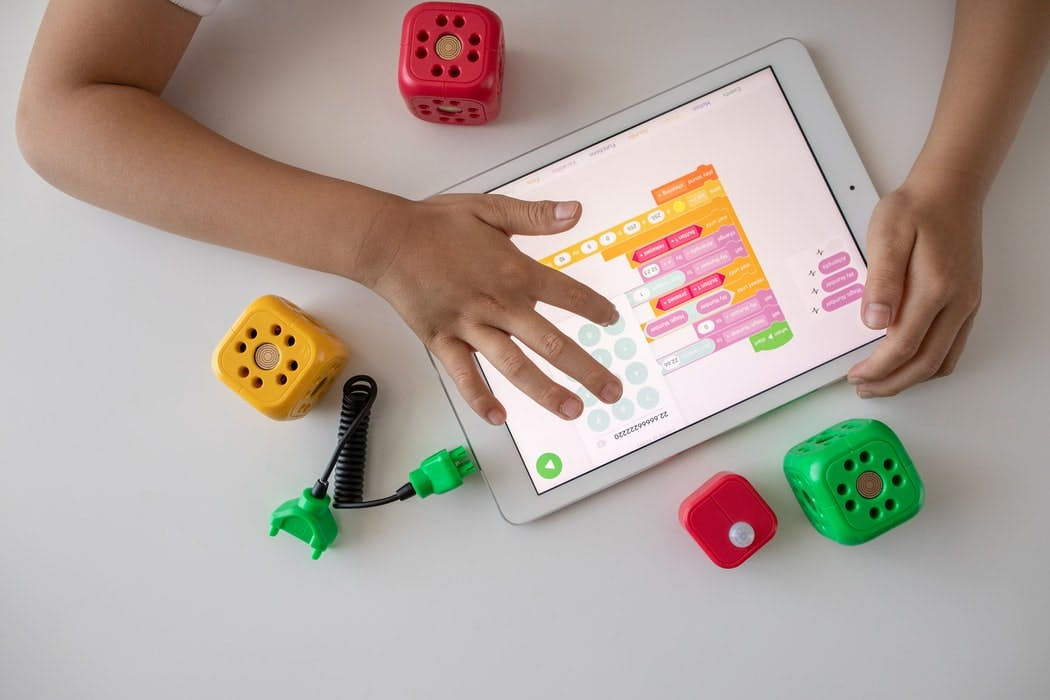 hands-on-tablet-play-interactive-game-with-toys-on-desk-robo-wunderkind-unsplash.jpg