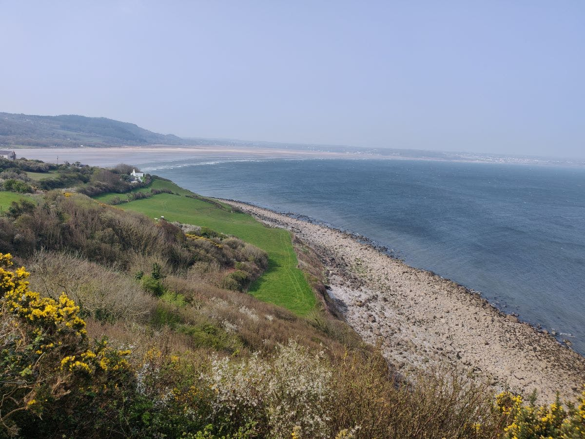 the view from a hillside overlooking the beach and sea on the Anglesey Coastal Path